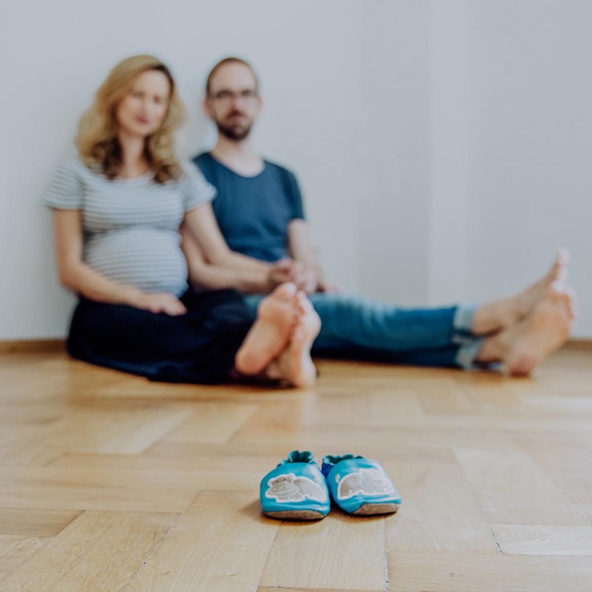 Schwangerschaft_Paar-auf-Boden_Babyschuhe_quadratisch