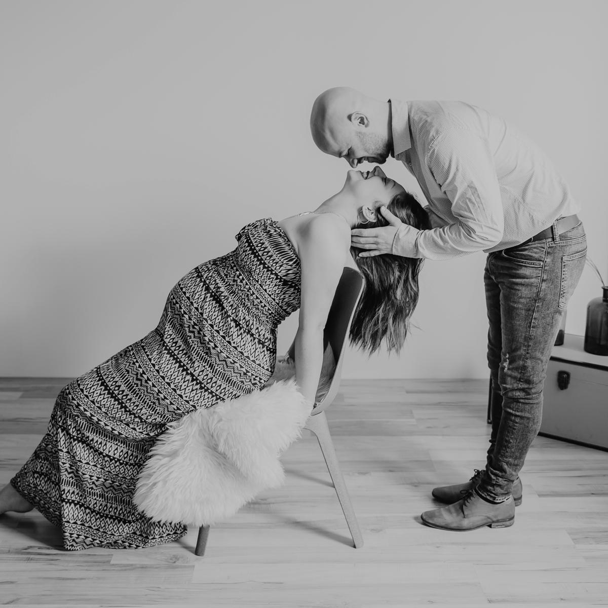 Schwangerschaft_Paar_küssend-auf-Stuhl
